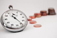 Stopwatch and money. Time makes money. one coin, two, three and etc Royalty Free Stock Image