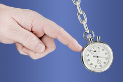 Stopwatch pendulum and hand. The hand shifts a pendulum consisting of a stop watch on a chain. Isolated on white [with clipping path Royalty Free Stock Photo