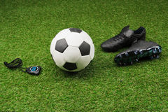 Stopwatch with soccer ball and boots on grass pitch Stock Photos