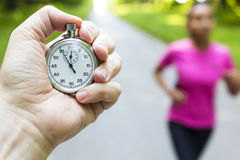 Stopwatch Timer and Young Woman Running. Classic stopwatch timer and young woman in pinkl running or jogging being timed on a road in summer royalty free stock photography