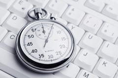 Stopwatch on white keyboard Royalty Free Stock Images