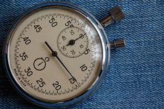 Stopwatch on worn blue jeans background, value measure time, old clock arrow minute and second accuracy timer record Royalty Free Stock Photos
