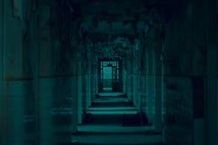 Stor övergiven korridor med stora brutna fönster och att exfoliate väggar i asylen royaltyfri fotografi