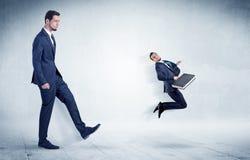 Stor affärsman som sparkar småföretagaren arkivfoto