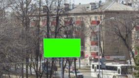 Stor affischtavla med en grön skärm nära den upptagna vägen med snabba rörande bilar Suddig abstrakt timelapsebakgrund arkivfilmer