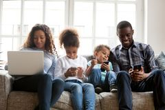 Stor afrikansk amerikanfamilj som använder apparater som tillsammans sitter arkivbild
