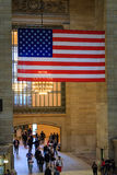 Stor amerikanska flaggan som hänger i den huvudsakliga folkhopen av den storslagna centralen Arkivfoto