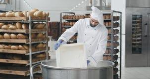 Stor bagare för bageribransch i en special likformig som förbereder degen att tillfoga något mer flytta sig för mjölbakgrundsarbe stock video