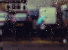 Stor bakgrundsbild med regndroppar och en flicka med ett blå paraply/flicka med ett paraply royaltyfria foton