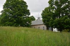 Stor baksida för New England ladugårdst i träd i Groton MOR Arkivfoto