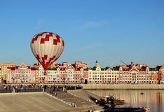 Stor ballong med en korg av folk i staden arkivbild