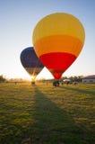 Stor ballong som två är klar att ta av på det gröna fältet Arkivfoto