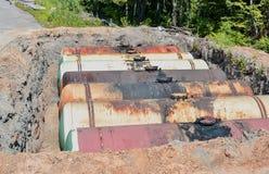 Stor behållare för bensin i det grävde villebrådet för lagring av oljaprodukter arkivbild