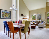 Stor beige ljus vardagsrum med matsaltabellen med olika färgstolar Royaltyfria Bilder