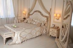 Stor bekväm dubbelsäng i elegant klassiskt sovrum royaltyfri fotografi