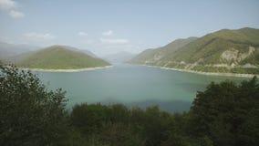 Stor bergsjö med turkos eller blått vatten, gröna kullar Vattenbehållare lager videofilmer