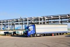 Stor blå lastbil med taxin och släpet på industrianläggningen på arkivfoto