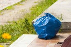 Stor blå plastpåse i bakgrunden av hotellet Arkivbild