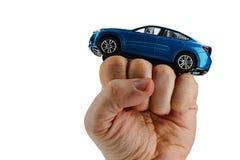 Stor blå SUV bilmodell som förläggas på den lyftta näven av den vuxna mannen, vit bakgrund Fotografering för Bildbyråer