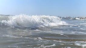Stor brisvågnärbild i ultrarapid som flyttar sig in mot kusten Sprejen från vågen glittrar i solen, och stock video