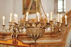 Stor bronsljuskrona i kristen kyrka arkivfoto
