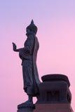 Stor buddha staty som går på skymningskyen Arkivfoton
