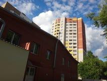 Stor byggnad, den blåa himlen och moln Arkivbild