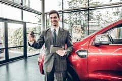 Stor choise! Stiligt ungt klassiskt bilförsäljareanseende på återförsäljaren som rymmer en tangent royaltyfri bild