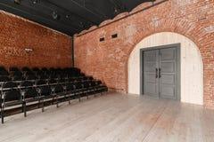 Stor dörr Vindstil Hall med svartstolar för webinars och konferenser Ett enormt rum med stora Windows som omges arkivfoto