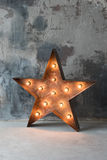 Stor dekorativ retro stjärna med massor av brinnande ljus på grungebetongbakgrund Härlig dekor, modern design arkivfoto