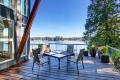 Stor dold och möblerad farstubro av det lyxiga huset med sikten av sjön royaltyfri foto