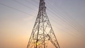 Stor elektricitetspol ural town för bergsimsolnedgång Royaltyfria Bilder