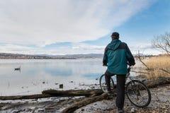 Stor europeisk sjö och cyklist med cykeln på kusten italy lakemaggiore arkivbild