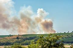 Stor f?ltbrand ?ver kullarna av en lantlig region arkivfoton