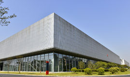 Stor fabriksbyggnad, stor modern byggnad, stor modern mässhall, under blå himmel, Arkivbild