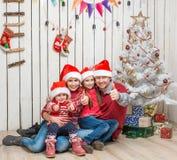 Stor familj i röda santa hattar nära julträdet Arkivbild