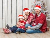 Stor familj i röda santa hattar nära julträdet Arkivfoton
