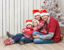 Stor familj i röda santa hattar nära julträdet Arkivbilder