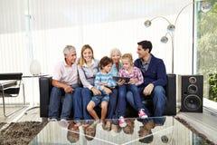 Stor familj med minnestavlaPC i vardagsrum Arkivfoto