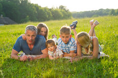 Stor familj på en grön äng Arkivfoto