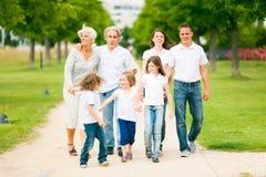 Stor familj som går till och med parkera royaltyfri foto