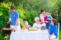 Stor familj som grillar kött för lunch Arkivbilder