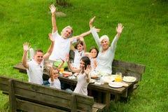 Stor familj som har en picknick i trädgården royaltyfria foton