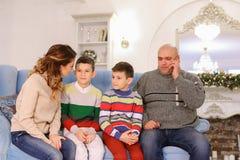 Stor familj som pratar på soffan, kvinna som talar på telefonen med verkligt Royaltyfri Fotografi