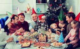 Stor familj som tillsammans äter under festlig julmatställe Royaltyfri Bild