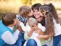 Stor familj som utomhus kramar och har roligt Arkivbilder