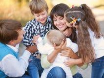 Stor familj som utomhus kramar och har roligt Royaltyfria Bilder