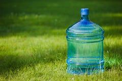 Stor flaska för vatten på gräs Arkivbild