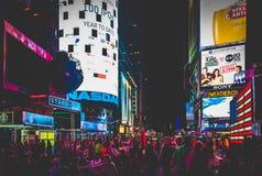 Stor folkmassa av folk i Times Square på natten, i midtownen Manha Arkivbild