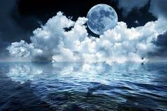 Stor fullmåne i natthimmel över havet som reflekterar i lugna vatten royaltyfri fotografi